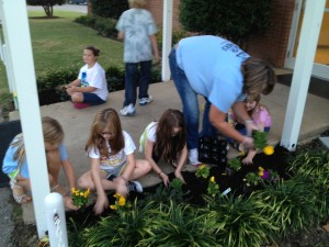 KWAM kids planting flowers around the church grounds.